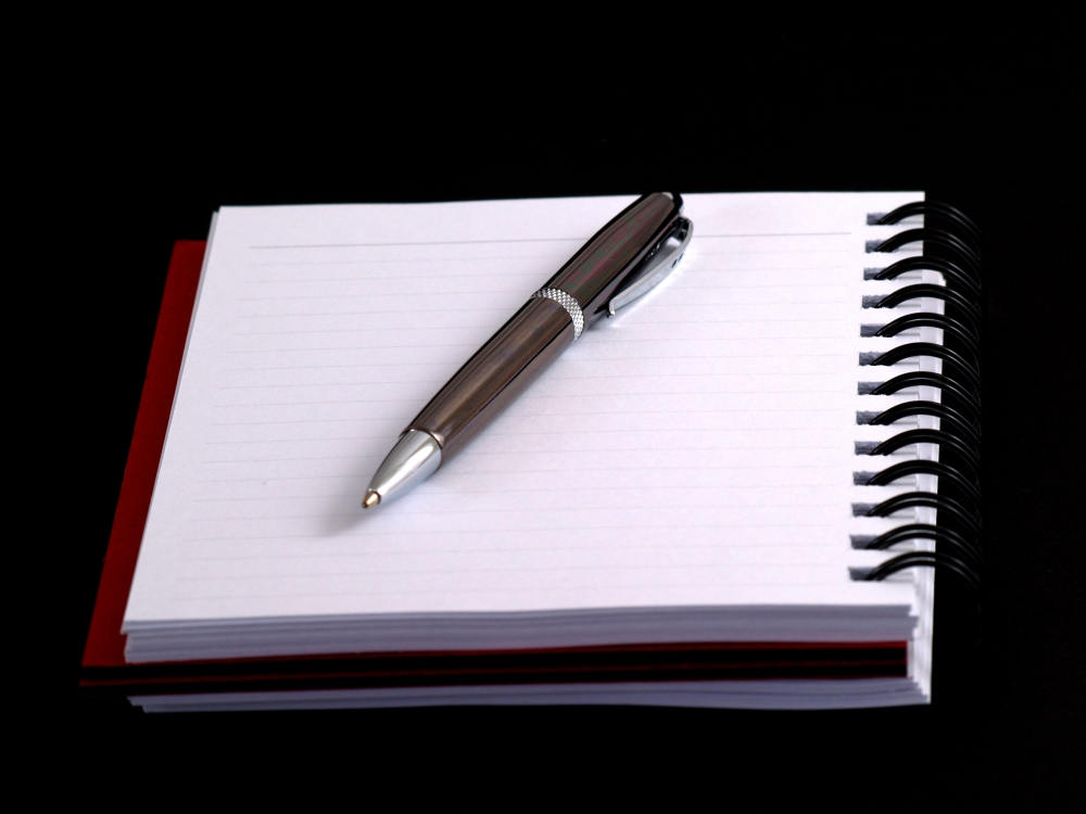 pen on notebook on black